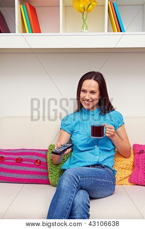 smiley woman watching tv and holding cup of tea