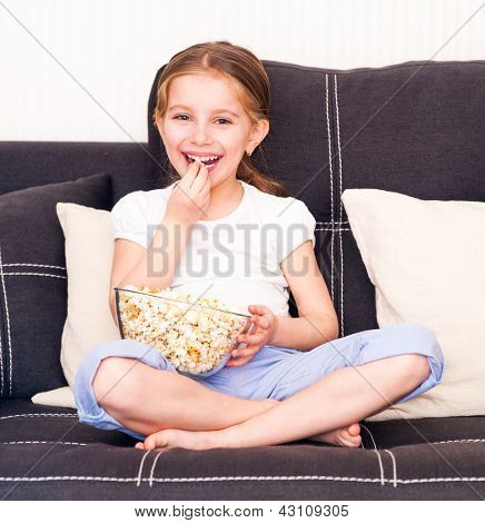little smiley girl eating popcorn in front of TV