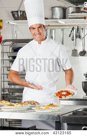 Portrait of happy male chef presenting pasta dish at commercial kitchen counter