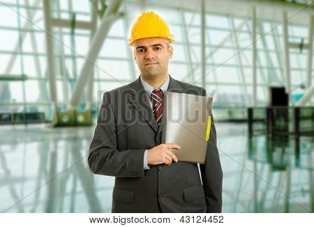An engineer with yellow hat at the office