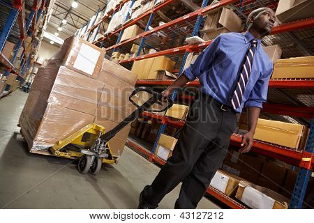 Man Pulling Pallet In Warehouse
