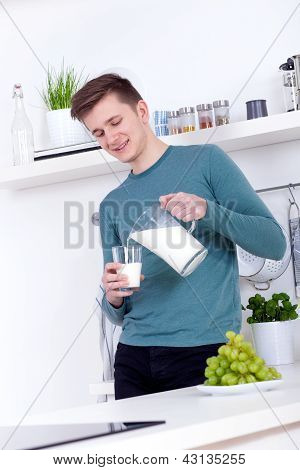 Young Man Drinking A Glass Of Milk In The Kitchen