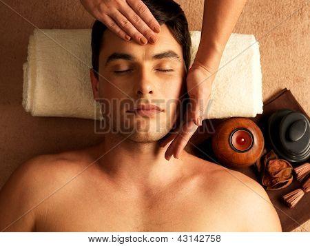 Hombre con masaje de cabeza en el salón de Spa