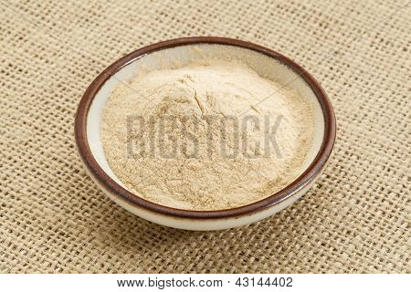 small ceramic bowl of African baobab fruit powder against burlap canvas