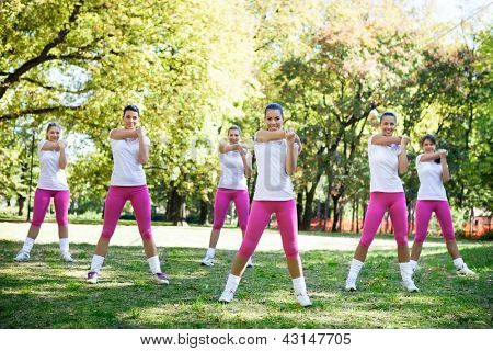 Group of women at the park stretching to warm up