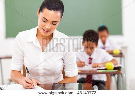 elegant female school teacher preparing lessons in classroom