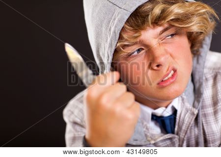 violent teen boy holding a knife on black background