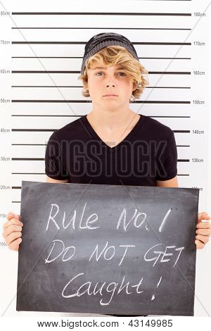 teen boy holding a blackboard criminal mug shot