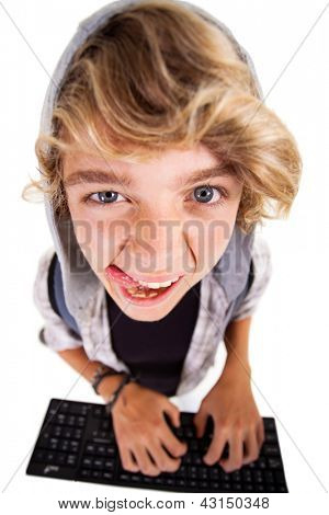 overhead view of a naughty teen boy playing on computer keyboard