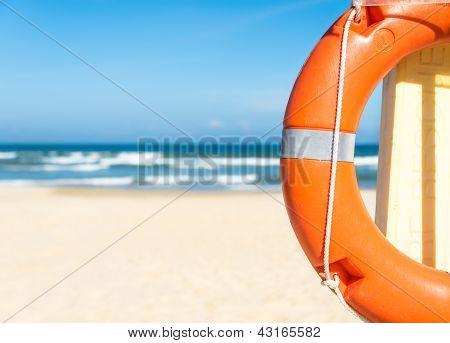 Seascape with lifebuoy, blue sky and sandy beach.
