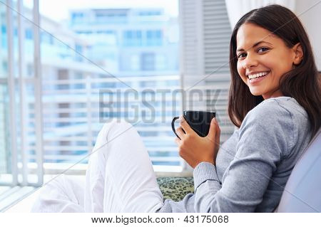 Woman enjoys fresh coffee relaxing at home on the sofa couch