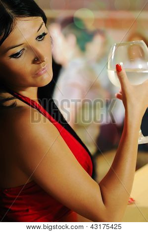 Lonely beautiful sad woman on party holding glass and drinking