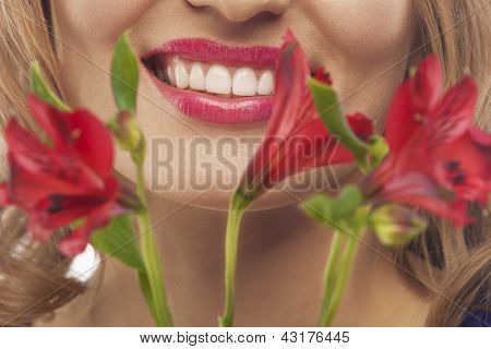 Closeup Of Face Of Young Smiling Woman With Bunch Of Flowers