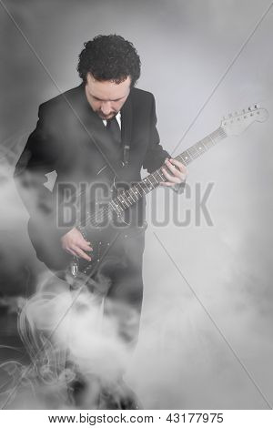 guitarist on stage full of smoke, man with black suit and guitar