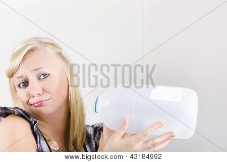 Unhappy Young Woman Holding Empty Milk Bottle
