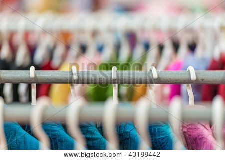 Rows of colorful clothes on hangers at shop.