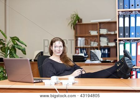 Woman Resting With Coffee Mug On Working Place With Legs On The Table
