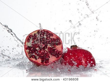 Juicy pomegranate with splashing water