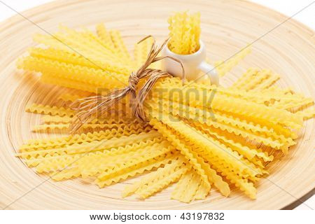 Pasta bunch composition on a wooden plate, closeup view