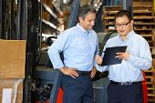 stock photo of forklift driver  - Businessmen Meeting By Fork Lift Truck In Warehouse - JPG