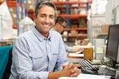 stock photo of packing  - Businessman Working At Desk In Warehouse - JPG