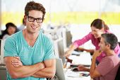 pic of spectacles  - Portrait Of Man Standing In Busy Creative Office - JPG