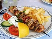 stock photo of souvlaki  - Plate with greek meal pork souvlaki in taverna - JPG