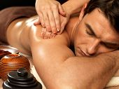 stock photo of shoulders  - Masseur doing massage on man body in the spa salon - JPG
