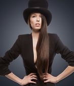 stock photo of crossdressing  - picture of woman in black jacket and top hat - JPG