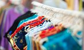stock photo of casual wear  - Rows of new colorful clothing on hangers at shop in foreground and background - JPG