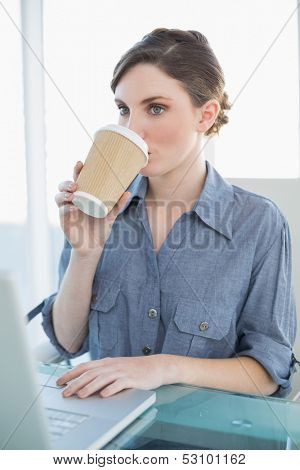 Beautiful businesswoman drinking of disposable cup sitting at her desk in front of her notebook