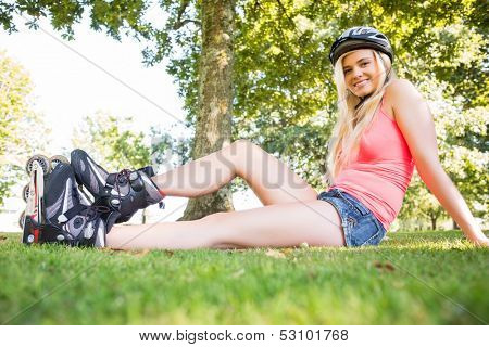 Casual smiling blonde wearing roller blades and helmet in a park