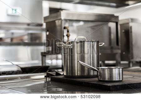 Pots standing on hotplate in professional kitchen