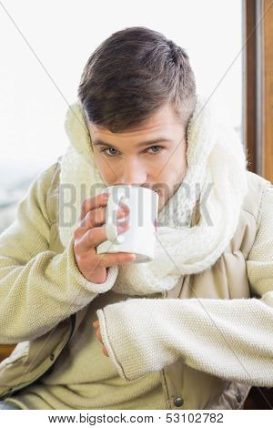 Close-up of a young man wearing earmuff while drinking coffee against cabin window