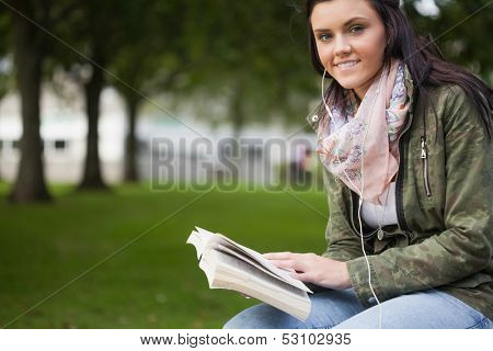 Gleeful brunette student sitting on bench reading on campus at college