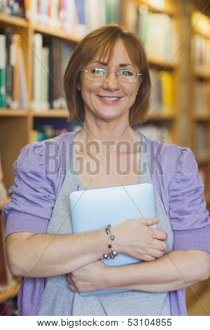 Mature female librarian posing in library holding a tablet smiling friendly at camera