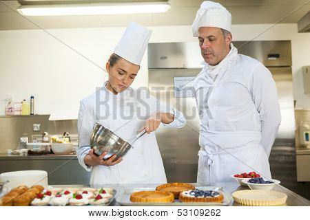 Serious chef whisking while being watched by head chef in professional kitchen