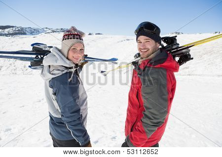 Rear view portrait of a smiling couple with ski boards standing on snow covered landscape