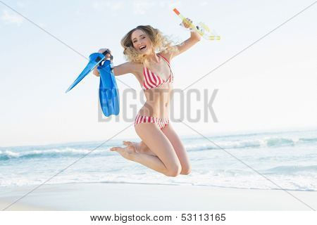 Cheerful woman jumping on beach while holding flippers and a snorkel and diving goggles