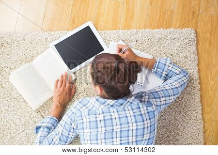 Brunette female student lying on the floor doing assignments using her tablet