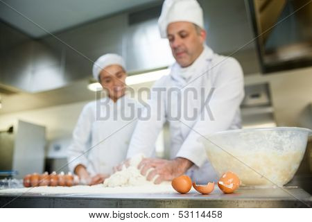 Head chef showing smiling trainee how to prepare dough in professional kitchen