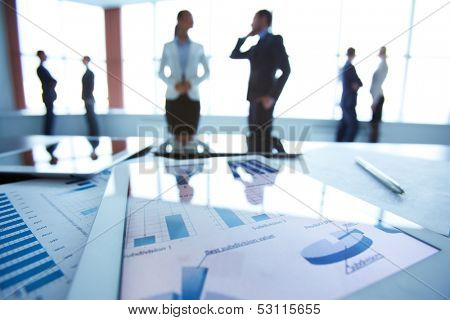 Close-up of business document in touchpad at workplace on background of office workers interacting