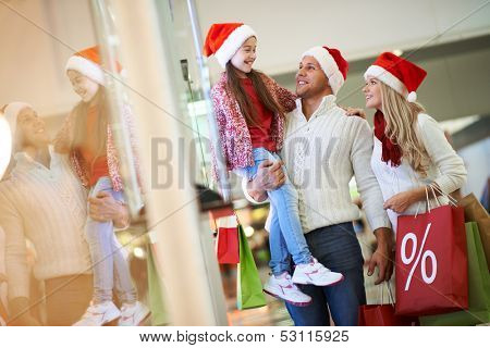 Portrait of happy family in Santa caps on Christmas sale in the mall