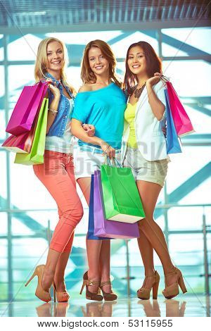 Portrait of three glamorous girlfriends with paperbags