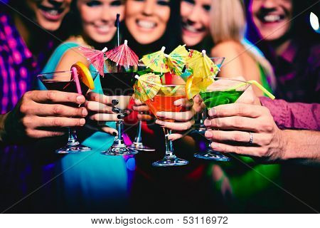 Glasses with cocktails held by happy friends at party