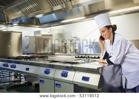 Young happy chef standing next to work surface phoning in professional kitchen