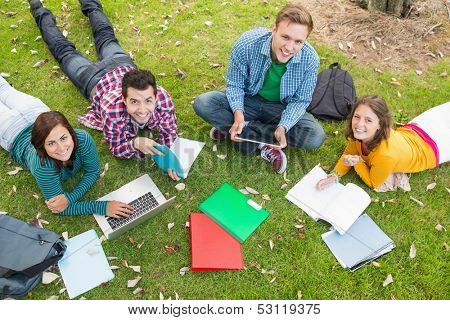 High angle portrait of young college students using laptop while doing homework in the park