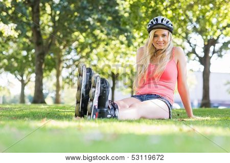 Casual happy blonde wearing roller blades in a park
