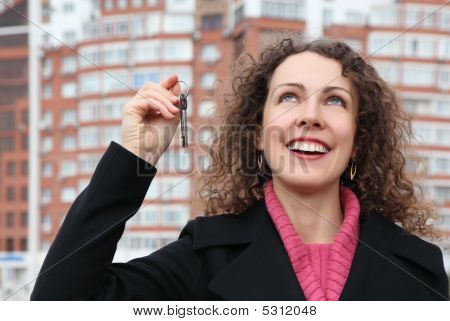 Young Girl With Key In Hand Looks Upwards Against Many-storeyed