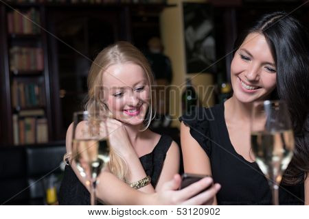 Two Women On A Night Out Using Mobile Phones